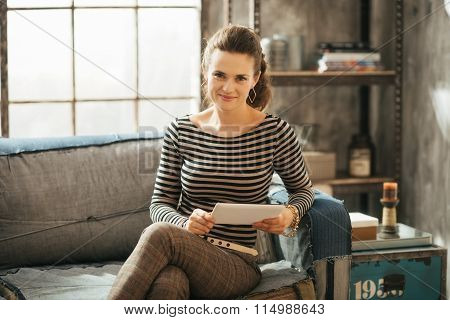 Young Wealthy Brunet Woman Sitting On Couch And Holding Tablet