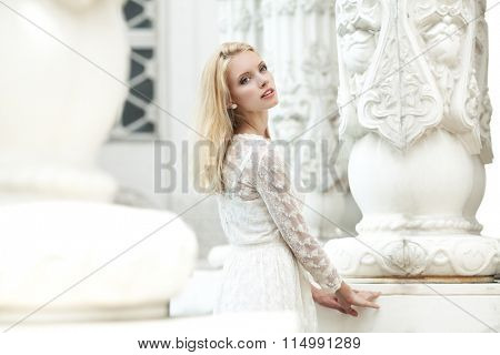 Beautiful young girl in a white lace dress outdoors