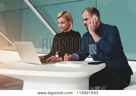 Man calling with mobile phone while his assistant searching needed information on laptop computer