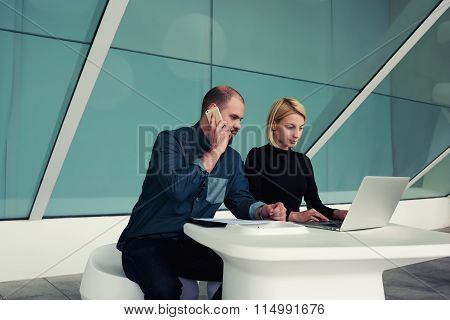 Young businessman talking on mobile phone with client while his secretary keyboarding on net-book