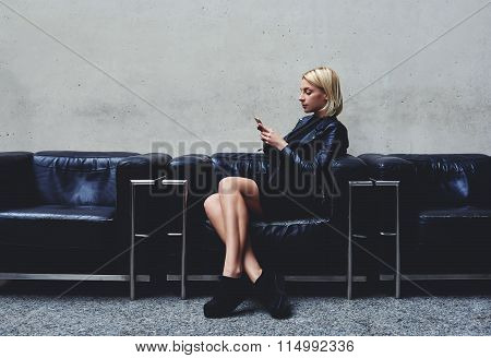 Young blonde woman reviewing traffic in Internet via cell telephone