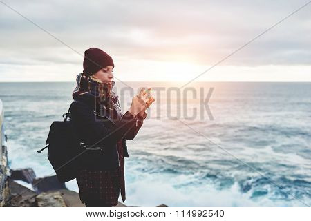Woman tourist dressed in stylish clothes shoots video of beautiful sea landscape on cell telephone