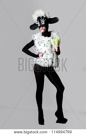 A Girl Dressed As A Sheep. The Unusual Costume And Body Painting.  Holds In The Hands Kale. A Woman