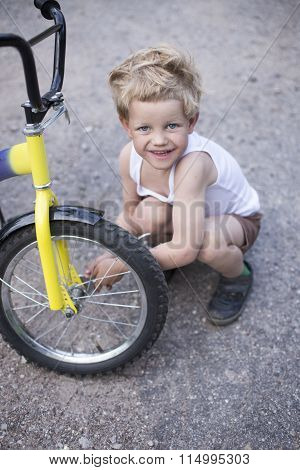 Boy Fixing Wheel Of Bike. Childhood.Cycling