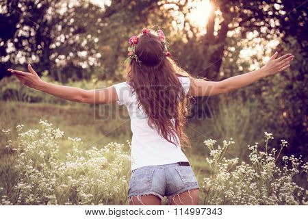 summer girl in jeans shorts and white t-shirt with open arms welcome nature, back shot, outdoor in field at sunset