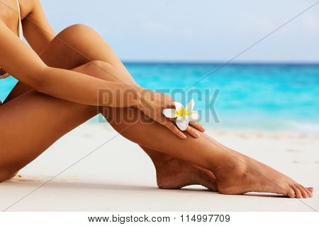 Women's beautiful sexy legs on the beach