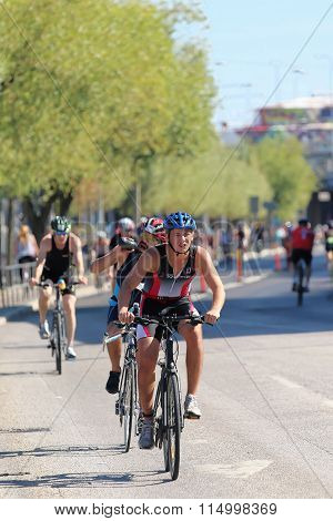 STOCKHOLM - AUG 23 2015: Cycling man followed by competitors trees in background at ITU World Triathlon event in Stockholm 2015