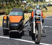 picture of sidecar  - Black and orange motercycle with sidecar in parking lot - JPG