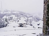 stock photo of velika  - Oriental-looking village and countryside under a snow blizzard;