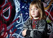 pic of deprivation  - child in front of graffiti wall in urban area - JPG