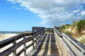 picture of off-shore  - Wooden dock with late afternoon shadows partition off sand dunes from Cape Charles Beach on the Island of Assateague Virginia - JPG