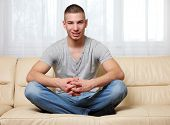 handsome man sitting yoga-pose at home
