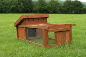 picture of chicken-wire  - wooden chicken house with wire mesh run attached standing on the grass in a field - JPG