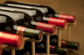 stock photo of wine bottle  - Red wine bottles stacked in rack on warm background