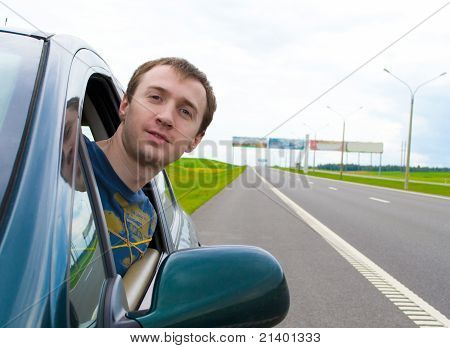 The Young Man Looks Out Of A Car Window On Road