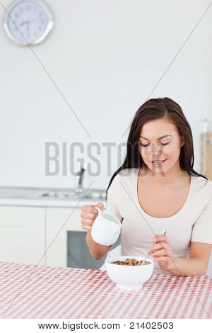 Portrait Of A Smiling Woman Pouring Milk In Her Cereal