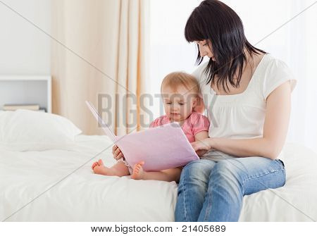 Beautiful Brunette Woman Showing A Book To Her Baby While Sitting On A Bed