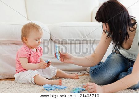 Beautiful Woman And Her Baby Playing With Puzzle Pieces While Sitting On A Carpet