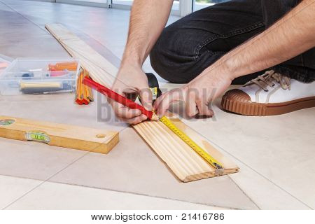 Man marking on plywood with measuring and pencil