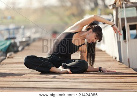 Outdoor Portrait of Beautiful Black-Haired Young Woman Exercising in Marina