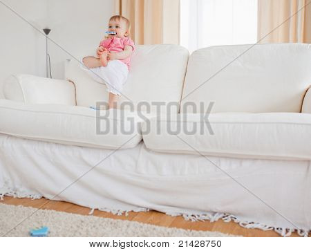 Lovely blond baby playing with puzzle pieces while standing on a sofa in the living room