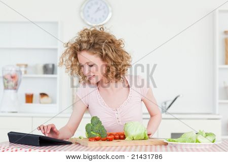 Beautiful blonde woman relaxing with her tablet while cooking some vegetables in the kitchen in her apartment