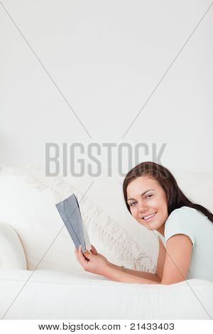 Portrait of a cute woman on a sofa holding a book looking at the camera