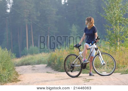 Young woman standing with bicycle on rural countryside road and looking back