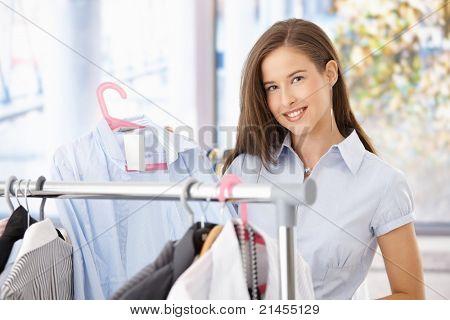 ¿Feliz mujer de compras, sosteniendo la camiseta en la tienda de ropa, sonriendo a la cámara.?