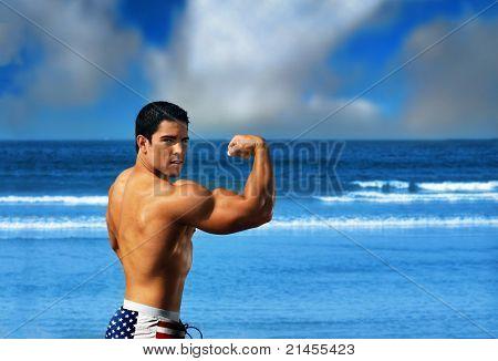 Joven musculoso sexy hombre fisicoculturista flexionando sus bíceps grandes en la playa contra un océano azul brillante