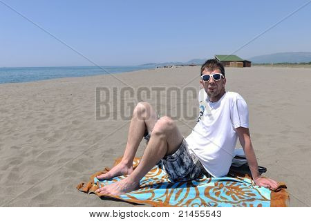 young man relaxing on beach at sunset