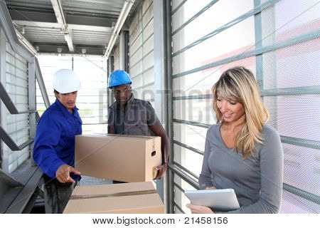 Businesswoman in warehouse controlling goods reception