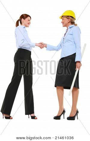 two businesswoman standing and shaking hands in white background