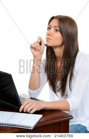 Pretty Businesswoman Thinking, With Laptop On The Table