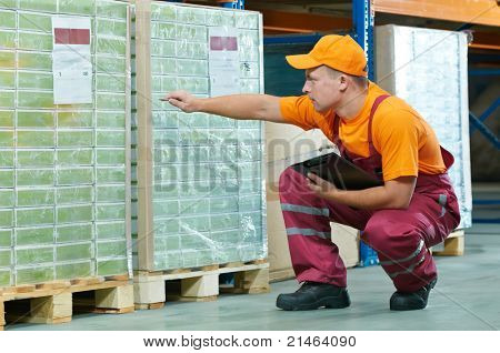 young worker man in uniform at warehouse checking rack arrangement of laminate flooring