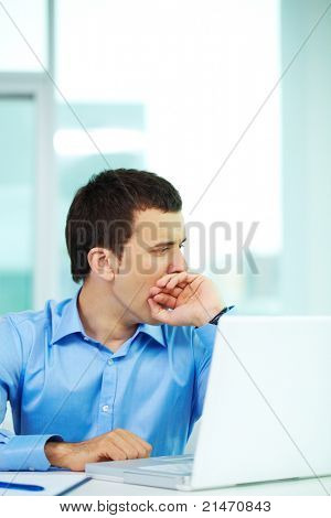 Portrait of bored businessman yawning in office