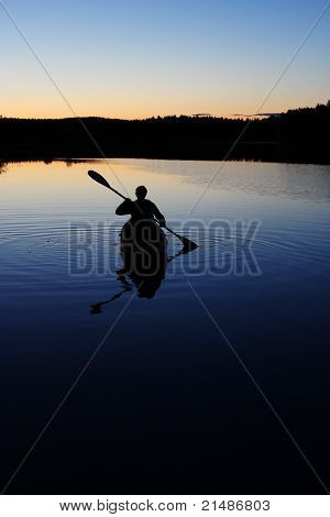 Sillouette of man kayaking on lake