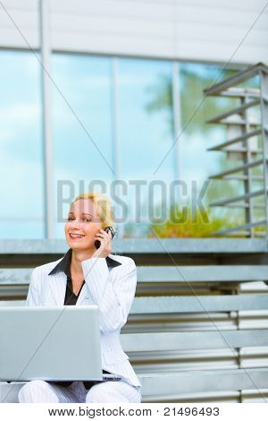 Smiling modern business woman with laptop sitting on stairs at office building and talking on mobile