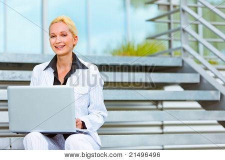 Smiling modern business woman sitting on stairs at office building and using laptop