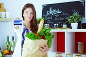 Woman with credit card and shopping bag in the kitchen at home . Woman with credit card poster