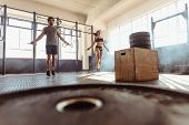 Fit Couple Jumping Ropes In Cross Training Gym poster