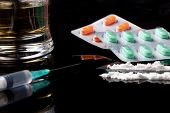 stock photo of overdose  - drugs and pills on black background with reflection - JPG
