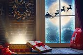 Merry Christmas! Magic gift box on the sill. Window decorated for holidays. Santa Claus flying in hi poster