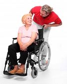 Happy elderly paraplegic woman sitting in a wheelchair and her male nurse.