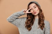 Picture of smiling young lady on winter warm hat isolated and looking camera make peace gesture. poster