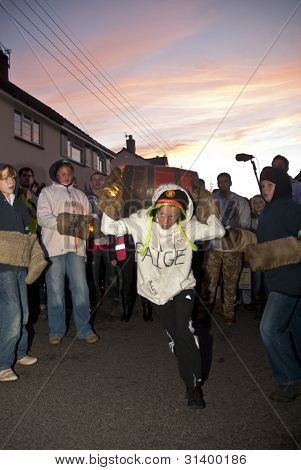 A Young Barrel Roller Runs Through The Crowd With A Burning Barrel At The 2011 Tar Barrels Of Ottery