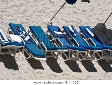 Blue Chairs In A Row On The Beach