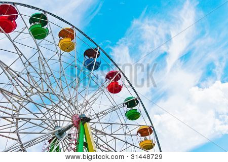 Colorful ferris wheel on blue sky background