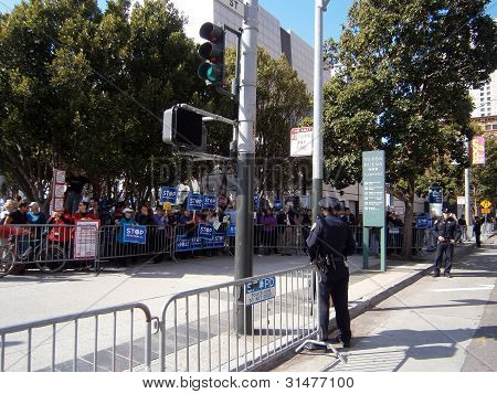 Sfpd Officers Stand On Street With Protesters Behind The Police Fence