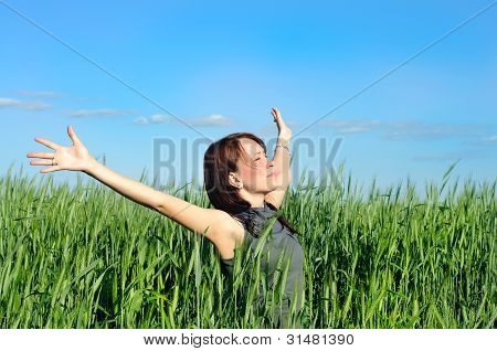 Woman With Hands Raised Up In The Wheat Field